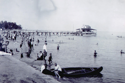 Photograph of boats and people sharing the beach